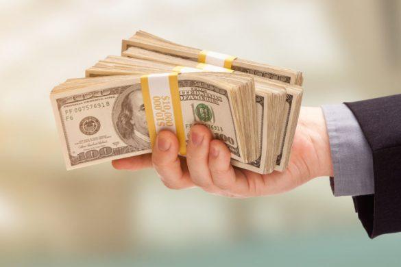hand holding a lot of dollars-انواع بازار های مالی